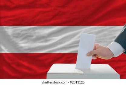 man putting ballot in a box during elections in austria