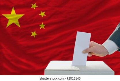 man putting ballot in a box during elections in china