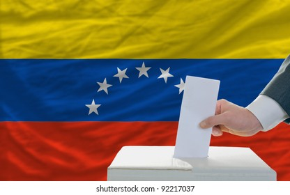 man putting ballot in a box during elections in venezuela in front of flag