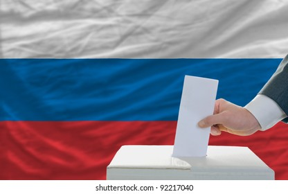 man putting ballot in a box during elections in russia in front of flag