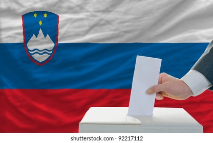 man putting ballot in a box during elections in slovenia in front of flag