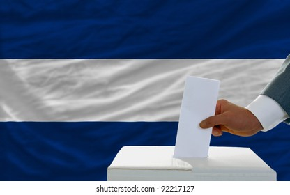 man putting ballot in a box during elections in nicaragua in front of flag