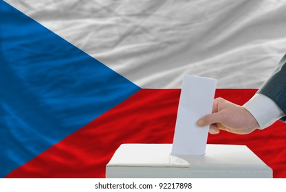 man putting ballot in a box during elections in czech in front of flag