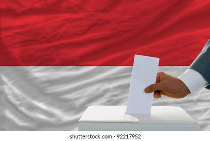 man putting ballot in a box during elections in indonesia in front of flag