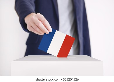 Man putting a ballot with French flag into a voting box.