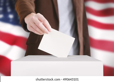 Man putting a ballot into a voting box. USA flag on a background. Toned image.