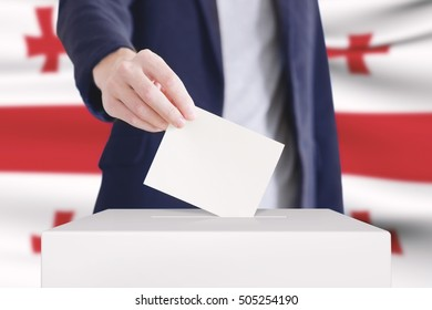 Man putting a ballot into a voting box with Georgian flag on background.