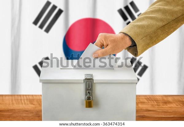 Man putting a ballot into a voting box - South Korea