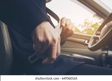 Man putting car seat belt before driving, close up at belt buckle, safe drive concept
