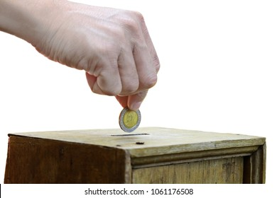 A Man putting coin into a wooden box as donation isolated on white background with clipping path.