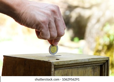 A Man putting coin into a wooden box as donation.