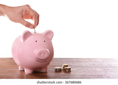 Man putting coin in pig moneybox
