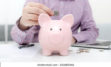 Man putting coin in piggy bank. saving money, budget, investment, finance concept