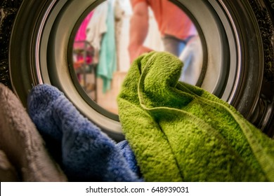Man putting color clothes into washing machine. inside view