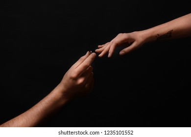 Man putting engagement ring on fiancee's finger on dark background