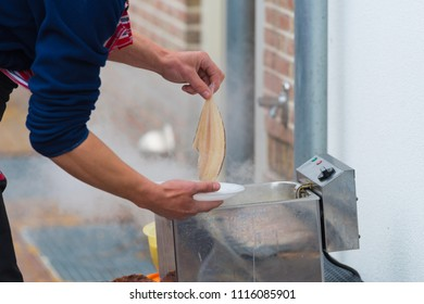 man putting fish in a frying pan
