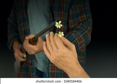 Man putting flowers in barrel of gun representing choosing peace over violence, mass murder, school shootings, and lax gun regulations and laws.