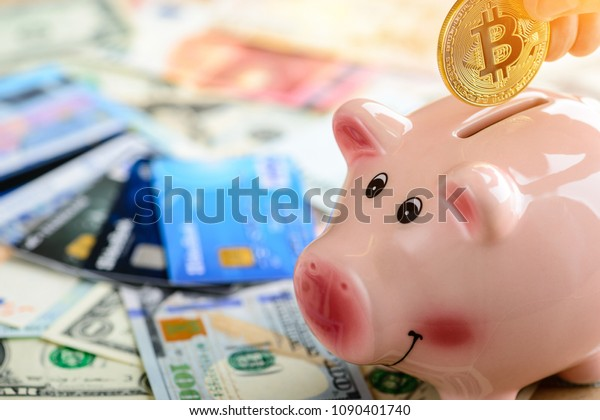 Man putting golden bitcoin coin in piggy bank  in rays of the sun. Concept of electronic virtual money for web banking, savings and international network payment