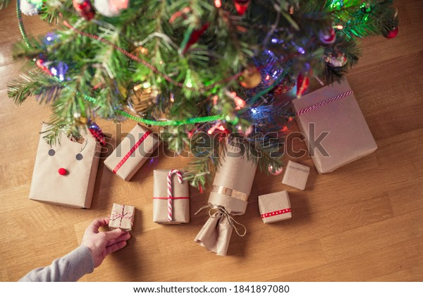 Man putting hand made gift wrapping in a kraft paper under christmas tree. Presents for family. Top view. Flat lay.