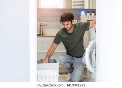 Man Putting his Laundry into a Washing Machine