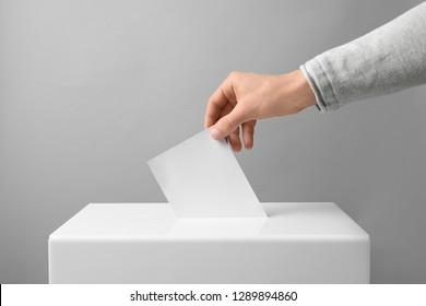 Man putting his vote into ballot box on light background, closeup