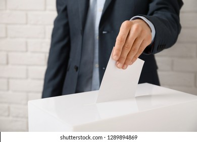 Man putting his vote into ballot box against brick wall, closeup