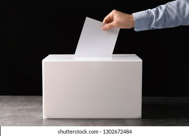 Man putting his vote into ballot box on table against black background, closeup