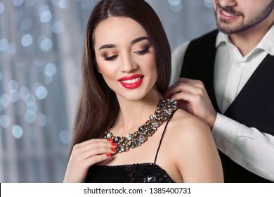 Man putting jewelry on beautiful young woman against blurred lights
