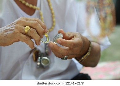 A man is putting a little Buddha image in locket.   Thai people are typically worn locket of Buddha image as a necklace.