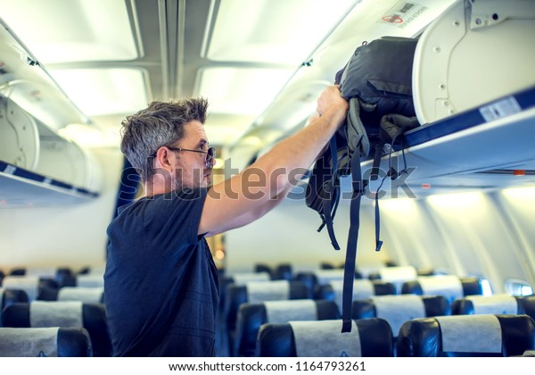 Man putting luggage on the top shelf on airplane. Travel concept