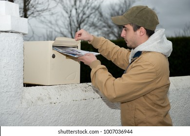 a man putting newspaper from the mailbox
