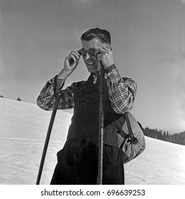 Man putting on glasses while holding ski poles