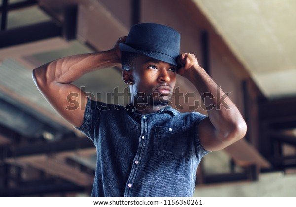 man putting on hat confident people successful person handsome guy