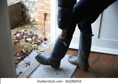 Man putting on his wellington boots