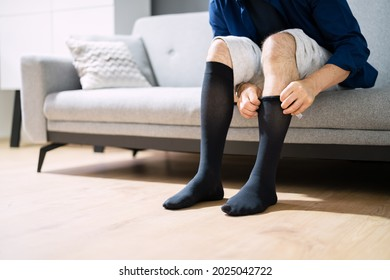Man Putting On Medical Compression Stockings On Legs