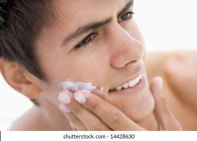 Man putting on shaving cream smiling