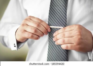 Man putting on tie clip, closeup, focused on clip.