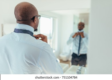 Man putting on a tie looking at a mirror. Back view of a businessman wearing a neck tie.