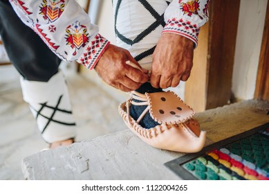 Man putting on  traditional bulgarian leather shoes - Tsarvuli