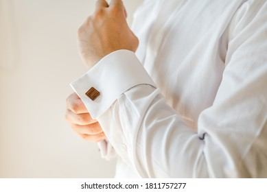 Man putting on a white shirt and cufflinks.  Preparation. Formal wear.