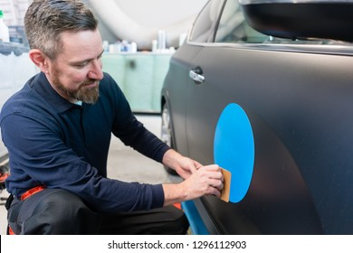 Man putting promotional sticker with company slogan on a car