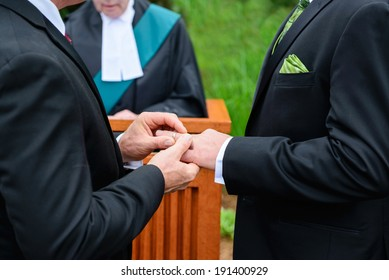 A man putting a ring on another man's finger during their wedding ceremony.
