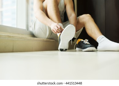 Man putting running shoes on.