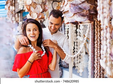 man putting a seashell necklace on a woman in traditional market