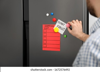 Man putting shopping list and reminder on refrigerator door, closeup