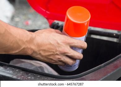Man putting spray bottle in recycling bin,Hazardous waste