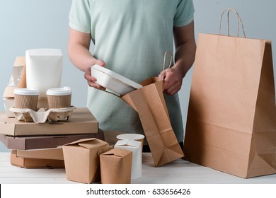 Man putting take-out food container into paper bag, close-up. Coffee cups in holder, pizzas, wooden surface, light grey background. Delivery.