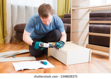 man putting together self assembly furniture .