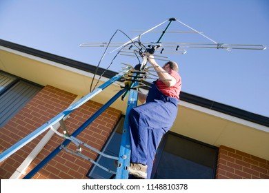A man putting up an TV antenna on his home.