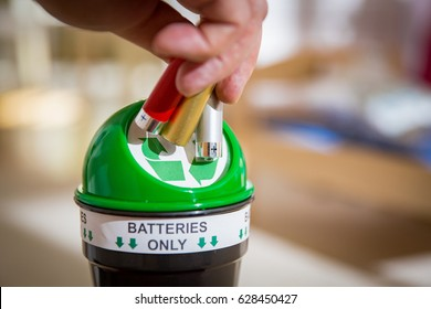 Man putting used batteries into recycling box at home. Child in the nursery room playing with toys. Separating waste concept. Batteries Only.